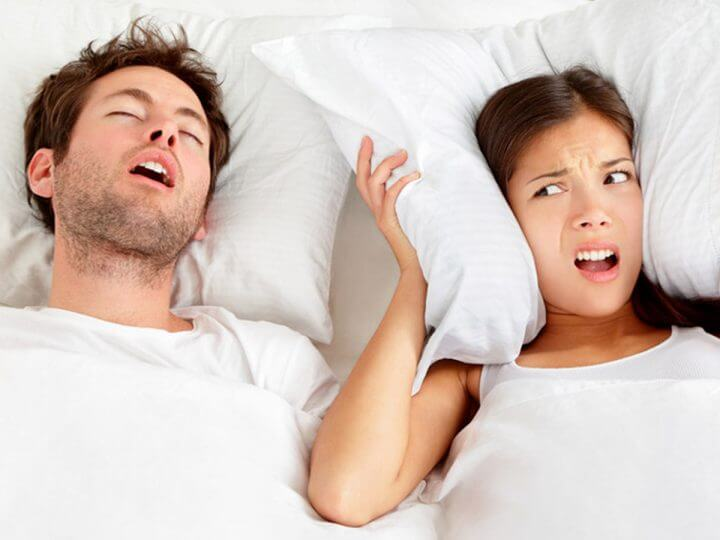 snoring man and angry woman holding pillow against her ears
