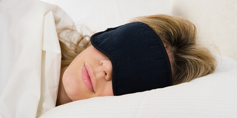 woman asleep in bed with a sleeping mask on
