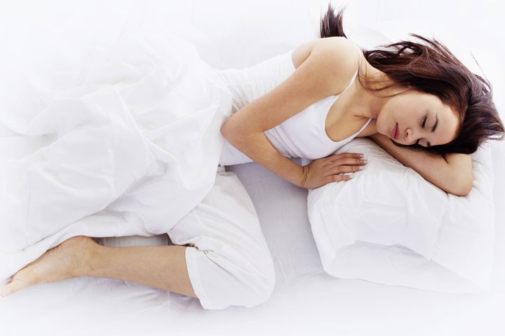 woman in a sleeping position on a white bed